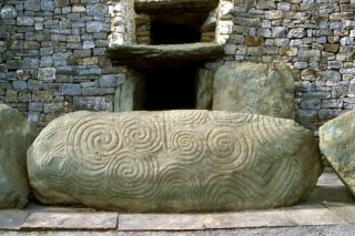 Newgrange Entrance stone which consists of a large triple spiral engraved with double loops which fill the left side