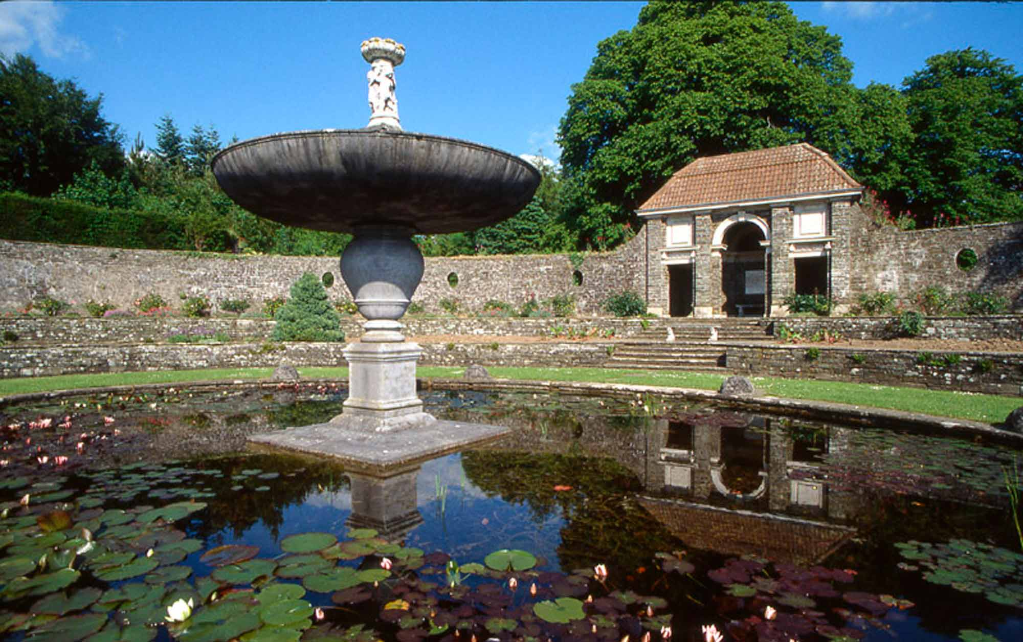 Close up of fountain and pond at Heywood Gardens with loggia in background with red tiled roof.