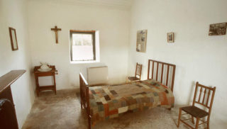 Bedroom in Pearse's cottage with frames on wall and crucifix