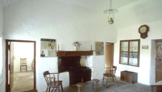 Kitchen inside Pearse's cottage with stove and cabinet with china
