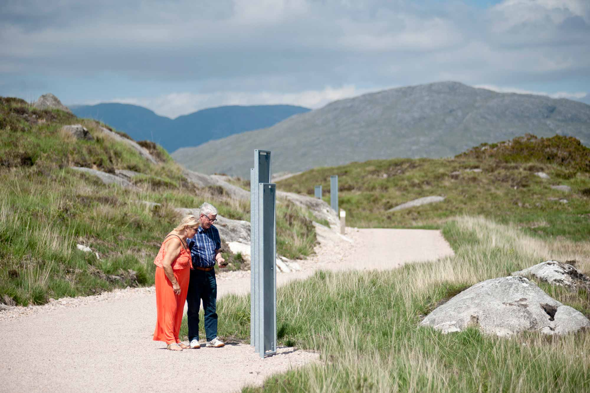 Two people stop at the wayfinding along the Ionad Cultúrtha an Phiarsaigh Walkways