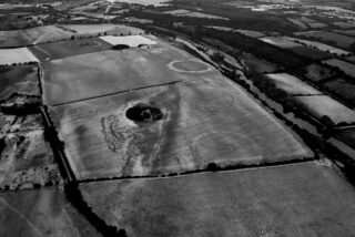View across the Newgrange floodplain from the west, showing the alignment of the henges (right). The dark linear band indicates differential crop growth over a major palaeochannel, within which there is an extant pond likely to have been of ritual significance in the Neolithic.