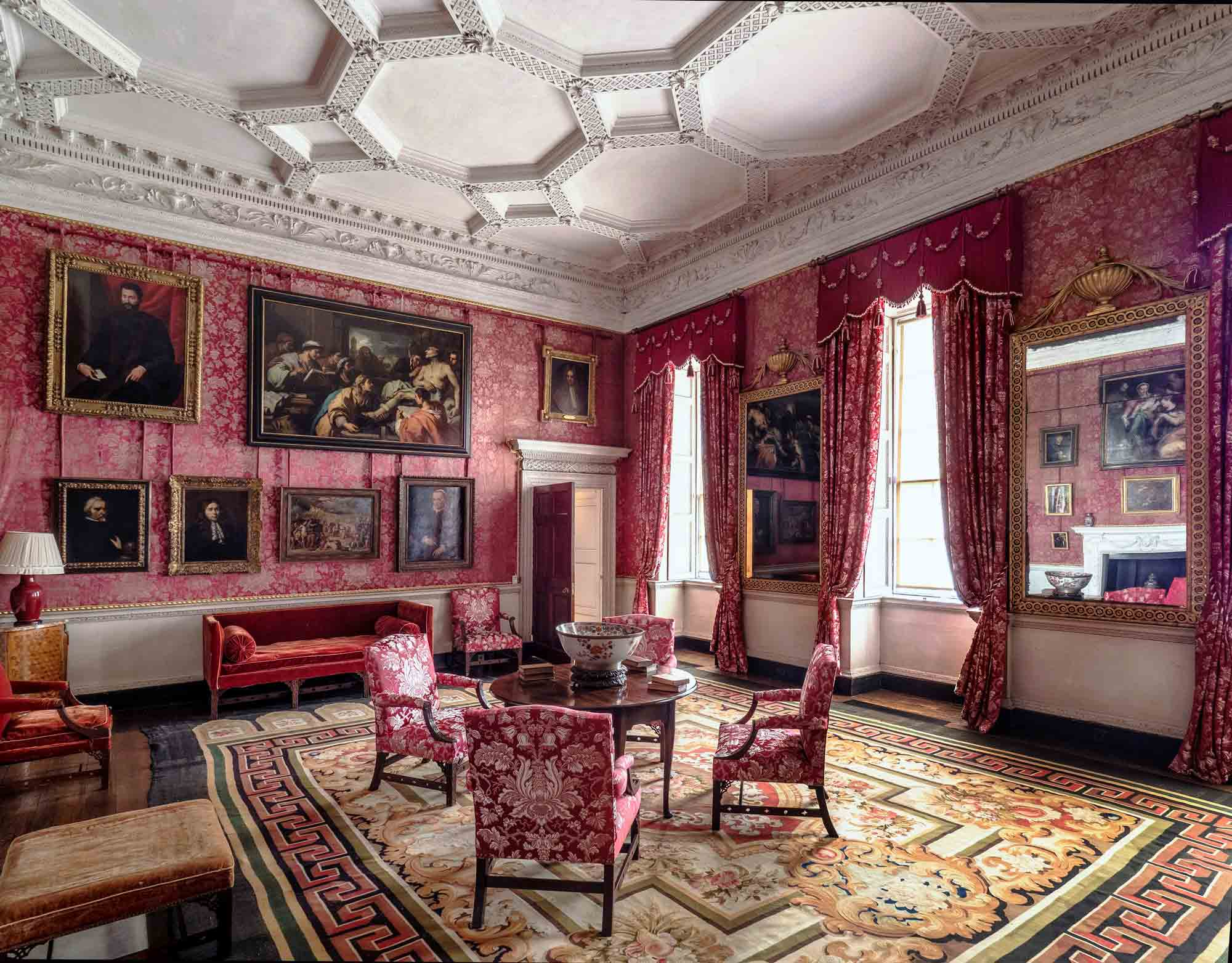 A glimpse of the Red Drawing Room after conservation of the silk wall hangings, showing the fabulous picture hang and the new curtains and upholstery made of silk reproduced to match the original