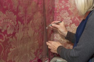 May Berkouwer shown infilling a split seam join on the West Wall with dyed silk crepeline and securing the panel with an adhesive Beva film strip